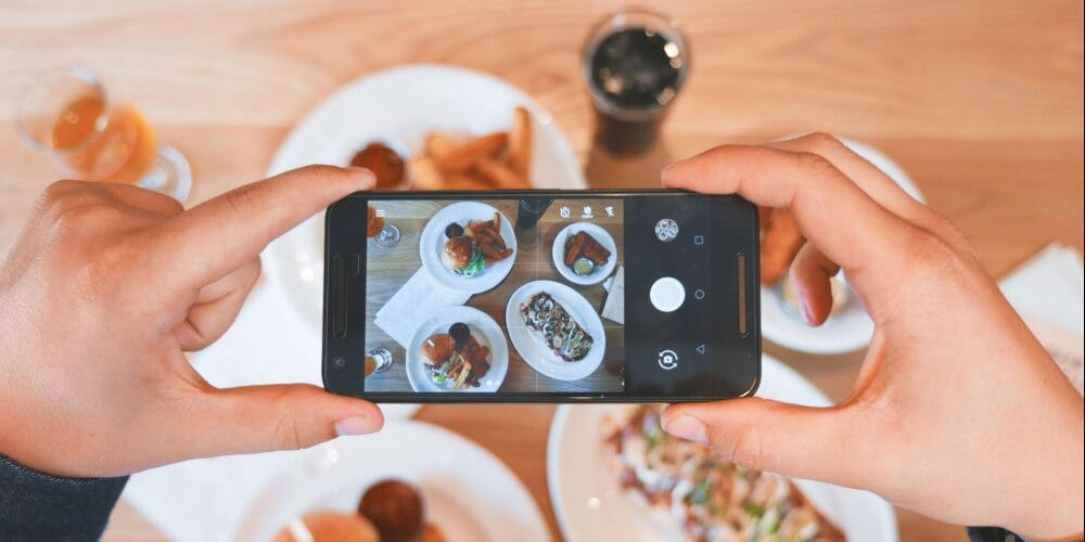 travel foodie influencer taking photo of food